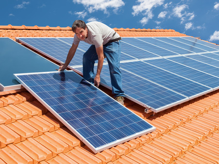 alternative: Man installing alternative energy photovoltaic solar panels on roof