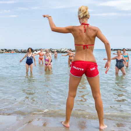 CATTOLICA, ITALY - JUNE 23: aquagym on the beach on June 23, 2014 in Cattolica, Emilia Romagna, Italy. A group of seniors doing gymnastics in the morning on the beach.