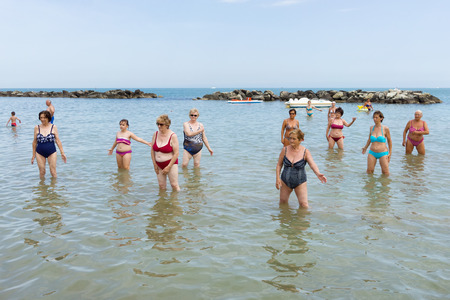aerobic treatment: CATTOLICA, ITALY - JUNE 23: aquagym on the beach on June 23, 2014 in Cattolica, Emilia Romagna, Italy. A group of seniors doing gymnastics in the morning on the beach.