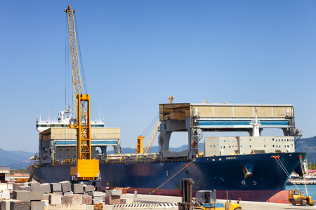 containership: loading cargo ship docked in industrial harbor Stock Photo