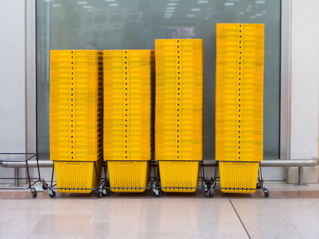 super market: pile of yellow shopping basket in super market