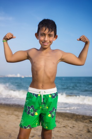 showing muscles: little boy showing his muscles on the beach