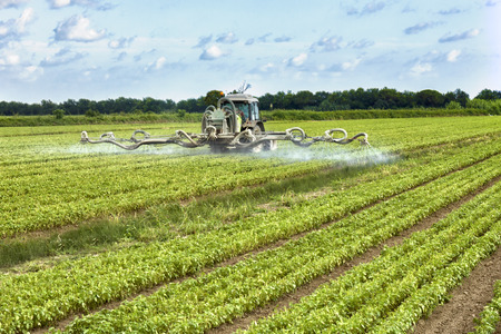 tractor spraying pesticides on a field