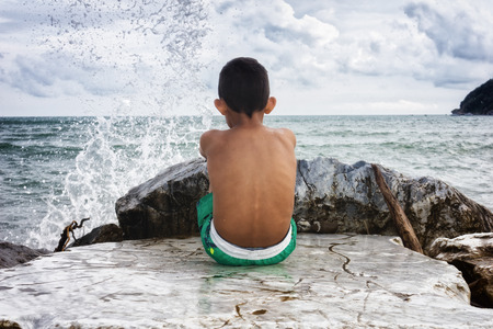 splash back: young boy looking at the sea