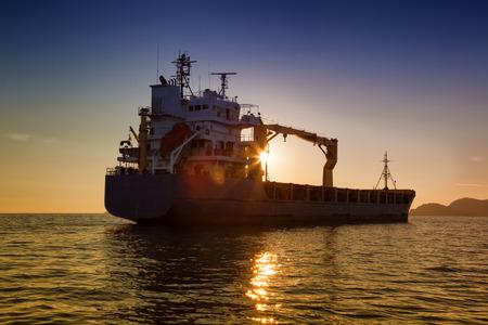 commerciële vrachtschip bij zonsondergang
