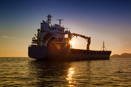 commercial cargo ship at sunset