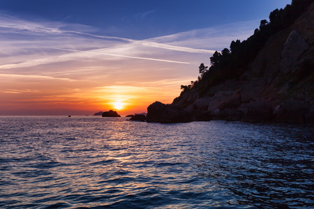 sunset on the Liguria sea in punta bianca, La Spezia, Italy photo