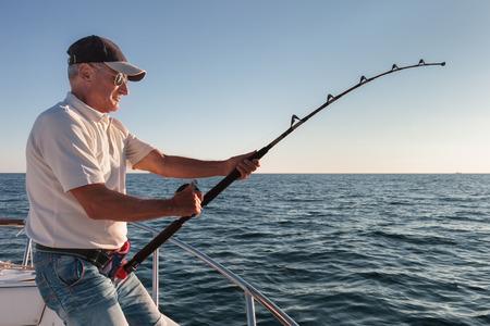 barca da pesca: pescatore pesca dalla barca Archivio Fotografico