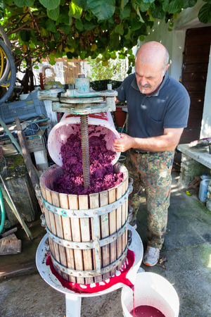 winemaking: man making red wine with classic press Stock Photo