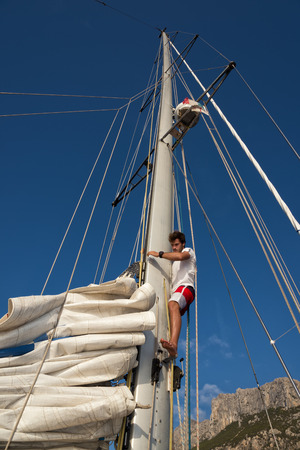 summer sport: young man working on sailing ship, active lifestyle, summer sport concept