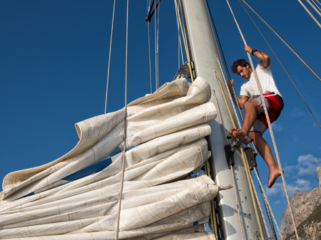 young man working on sailing ship, active lifestyle, summer sport concept