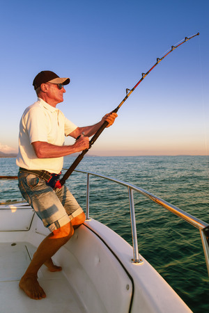 Angler fisherman fighting big fish on the ocean from the boat 스톡 콘텐츠