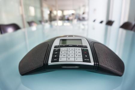 Inside modern conference room, focus on phone Standard-Bild