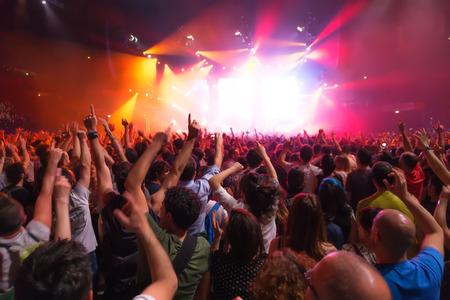 menigte van mensen op concert in de voorkant van het podium met verlichting