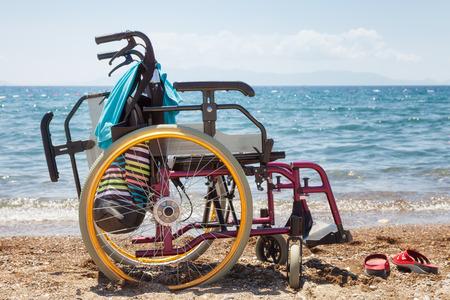 rolstoel op het strand tegen blauwe zee in de zomer Stockfoto