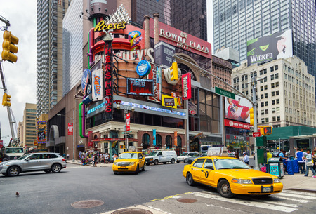 NEW YORK CITY - JUNE 15, 2015: Yellow cabs in Broadway, a busy tourist intersection of commerce Advertisements and theaters. One of the most famous streets of New York City and US