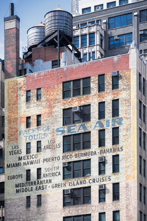 brownstone: NEW YORK CITY - JUNE 14, 2015: faded ads on old brick building on the Eighth Avenue and 39th Street