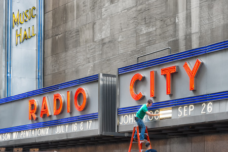 venue: NEW YORK CITY - JUNE 17, 2015: worker changing advertising of Radio City Music Hall, an entertainment venue located in Rockefeller Center