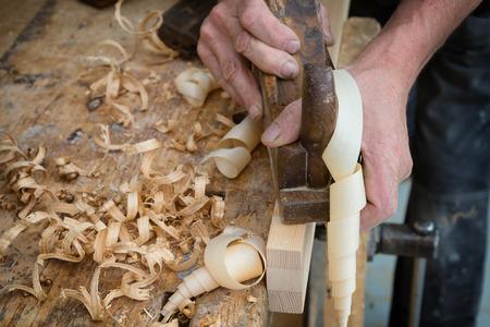 carpintero: Carpintero Senior o carpintero haciendo trabajar la madera en una tabla de madera en el taller con el plano Manual