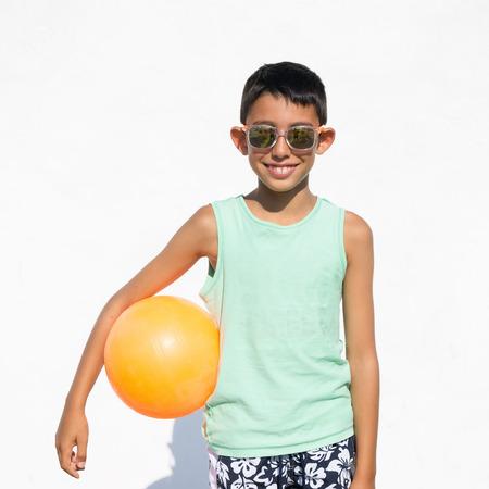 pelota de voley: muchacho joven con voleibol de playa y gafas de sol en el fondo blanco