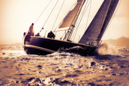 sailing ship: sail boat sailing on sunset Stock Photo