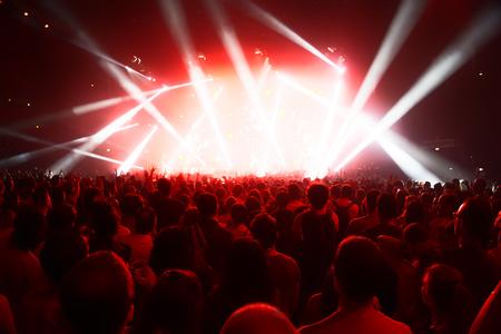 祭り: 明るいステージ ライトの前で若い人たちのコンサートの群集 報道画像