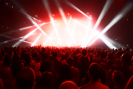 festivals: concert crowd of young people in front of bright stage lights Editorial