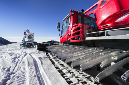 groomer: snowmaking gun and snow groomer on ski slopes Stock Photo