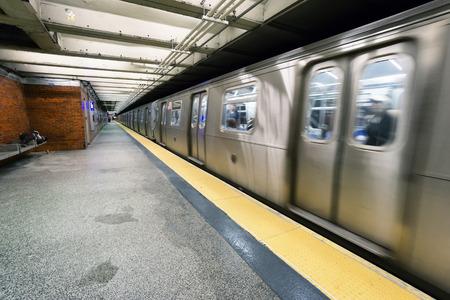 subway station: NEW YORK CITY - JUNE 13, 2015: train on New York City subway with homeless sleeping on the platform Editorial