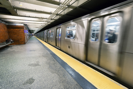 NEW YORK CITY - JUNE 13, 2015: train on New York City subway with homeless sleeping on the platform Editorial