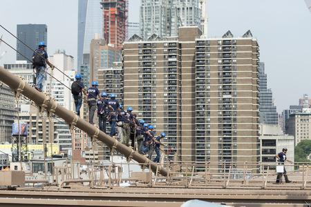 new construction: NEW YORK CITY, USA - JUNE 12, 2015: NYPD ESU officers climb down the brooklyn bridge