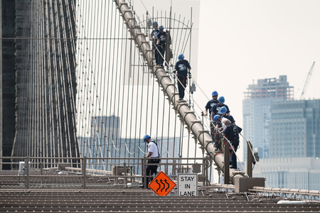 climbing cable: NEW YORK CITY, USA - JUNE 12, 2015: NYPD ESU officers climb down the brooklyn bridge