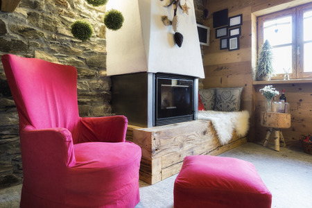 furniture design: Cozy interior of a rustic chalet with modern fireplace Stock Photo