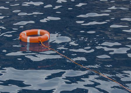 Anillo de vida flotando en la parte superior del agua azul del océano Foto de archivo - 96083586