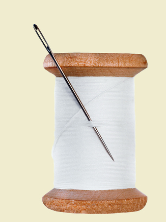 sewing threads spool with sewing needle,isolated on light yellow background Stock Photo