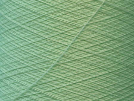 texture of light green synthetic thread in spool