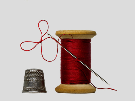 sewing threads spool with sewing needle and thimble isolated on white background