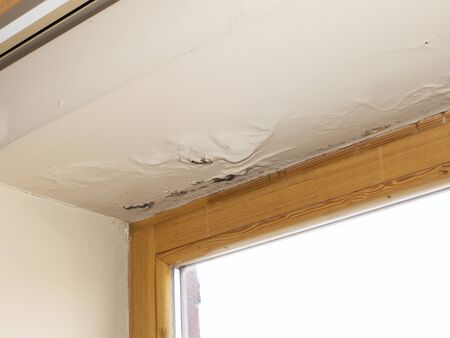 water damaged ceiling next to window