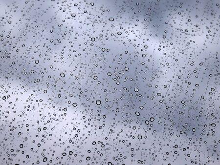 Raining, dark clouds, water drops on window glass Фото со стока