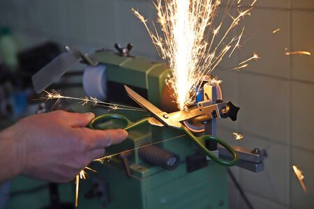 scissors sharpening in the workshop, workers hands, sparkles Фото со стока