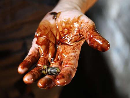 screw in engine oil dirty hand, repairman Фото со стока