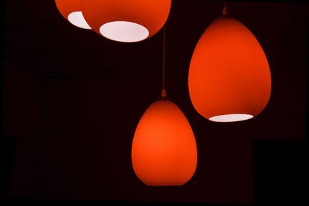 suspend: Four red modern lamps in a black room