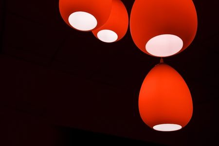 Four red modern lamps in a black room