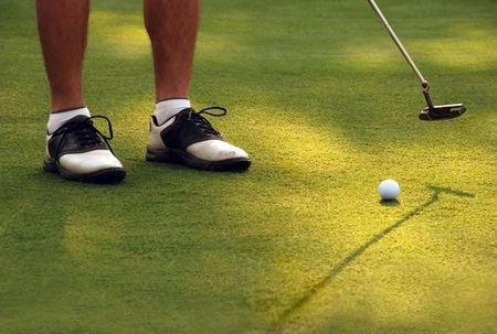 A golfer putting a ball Фото со стока