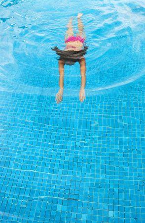 A young woman swimming in a pool Фото со стока