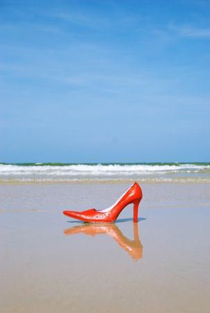A red and pink stiletto shoe on a beach photo