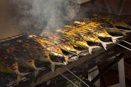 Fish being grilled in a market in Malaysia Фото со стока
