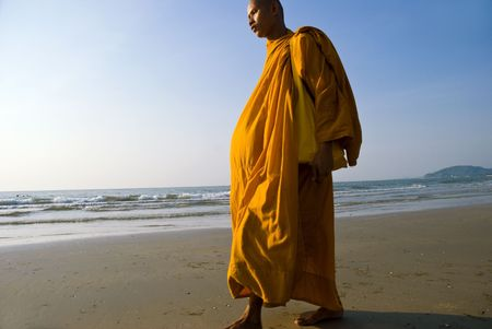 A Buddhist monk walking on a beach in Thailand