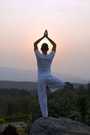 A man welcoming the sun with prayer Фото со стока