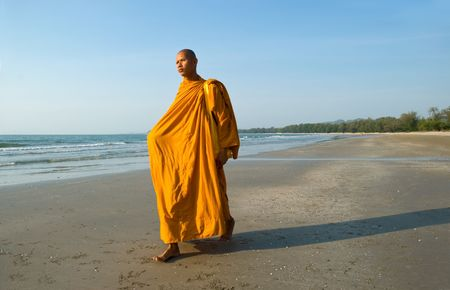 A Thai Buddhist Monk walking on the beach in the early morning sun photo